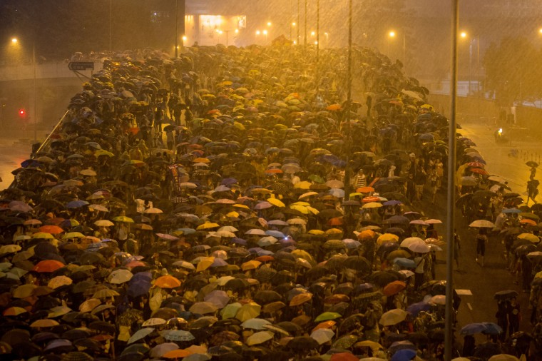 Thousands of protesters shelter under umbrellas from heavy rain aftera thunderstorm passed over outside the Hong Kong Government Complex on September 30, 2014 in Hong Kong, Hong Kong. Thousands of pro democracy supporters continue to occupy the streets surrounding Hong Kong's Financial district. Protest leaders have set an October 1st deadline for their demands to be met and are calling for open elections and the resignation of Hong Kong's Chief Executive Leung Chun-ying. (Photo by Chris McGrath/Getty Images)