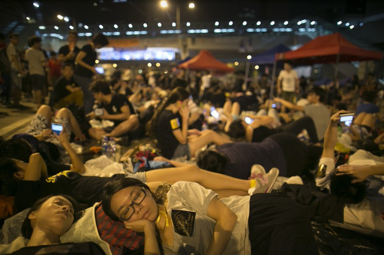 Student protesters sleep on the streets on October 1, 2014 in Hong Kong, Hong Kong. Thousands of pro-democracy supporters continue to occupy the streets surrounding Hong Kong's Financial district. Protest leaders have set an October 1st deadline for their demands to be met and are calling for open elections and the resignation of Hong Kong's Chief Executive Leung Chun-ying. (Photo by Paula Bronstein/Getty Images)