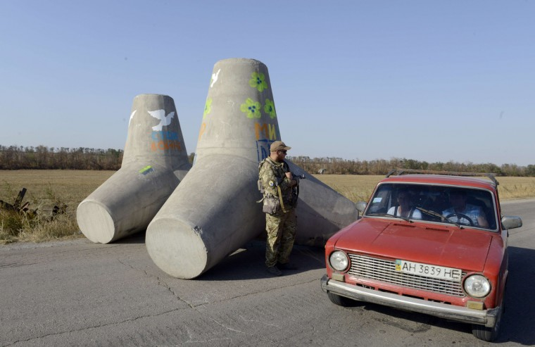 A Ukrainian fighter from the Azov Battalion stands guard near concrete barriers across the road on a checkpoint on the outskirts of Mariupol. Mariupol, a large city of about 500,000 people, is located about 50 kilometres (30 miles) from the Russian border and about 35 kilometres from Novoazovsk, which has been taken over by pro-Russian rebels. (Alexander Khudoteply/Getty Images)