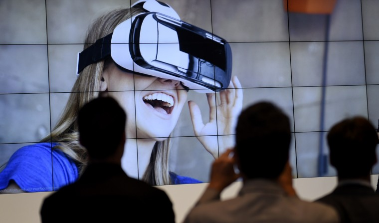 """Visitors attend a presentation of the virtual reality headset Gear VR at the booth of South Korean electronic giant Samsung on the opening day of the consumer electronics trade fair """"Internationale Funk Ausstellung """"(IFA) in Berlin one of Europe's biggest showcases of the latest electronic gadgets runs until September 10, 2014. (Tobias Schwarz/AFP/Getty Images)"""