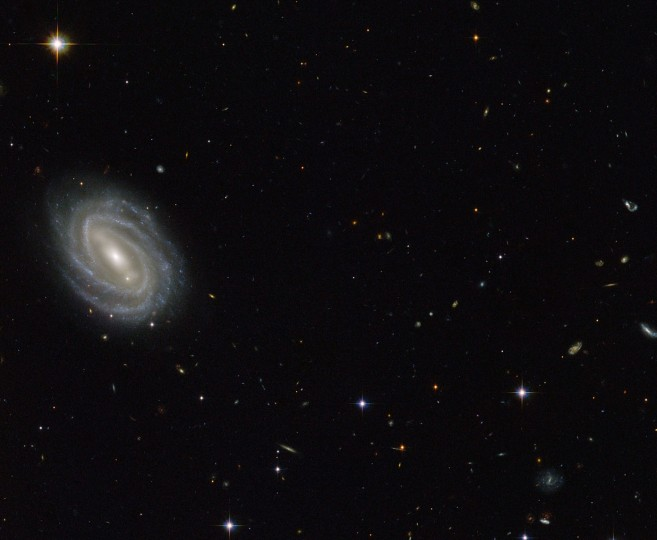 "This NASA/ESA Hubble Space Telescope image obtained September 8, 2014 shows a spiral galaxy known as PGC 54493, located in the constellation of Serpens (The Serpent). This galaxy is part of a galaxy cluster that has been studied by astronomers exploring an intriguing phenomenon known as weak gravitational lensing. This effect, caused by the uneven distribution of matter (including dark matter) throughout the Universe, has been explored via surveys such as the Hubble Medium Deep Survey. Dark matter is one of the great mysteries in cosmology. It behaves very differently from ordinary matter as it does not emit or absorb light or other forms of electromagnetic energy hence the term ""dark"". Even though we cannot observe dark matter directly, we know it exists. One prominent piece of evidence for the existence of this mysterious matter is known as the ""galaxy rotation problem"". Galaxies rotate at such speeds and in such a way that ordinary matter alone the stuff we see would not be able to hold them together. The amount of mass that is ""missing"" visibly is dark matter, which is thought to make up some 27 percent of the total contents of the Universe, with dark energy and normal matter making up the rest. PGC 55493 has been studied in connection with an effect known as cosmic shearing. This is a weak gravitational lensing effect that creates tiny distortions in images of distant galaxies. (NASA)"
