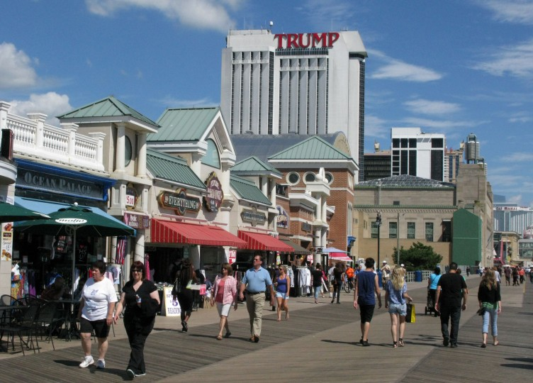 People walk on the boardwalk near the Trump Plaza Casino September 15, 2014 in Atlantic City, New Jersey. The Trump Plaza, which opened on May 14, 1984, shut down September 16, 2014, the fourth casino to shutter its doors this year, and a fifth casino, the Trump Taj Mahal, may close if it cannot cut costs of operation. The massive contraction, following years of customer losses to surrounding states, is eliminating 8,000 jobs, or about a quarter of the industry's employment in Atlantic City. (Don Emmert/AFP/Getty Images)