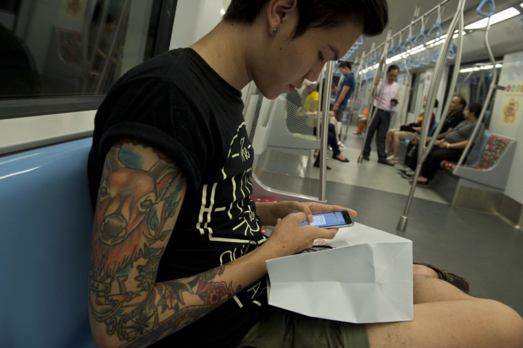 Singaporean student Perry Zhao checks his newly purchased iPhone 6 inside a MRT commuter train after its launch by Singtel, Singapore telecommunication company in Singapore on September 19, 2014. Singapore is one of the first markets in the world to take delivery of the latest iPhone models which feature large screen handsets. Romeo Gacad/AFP/Getty images