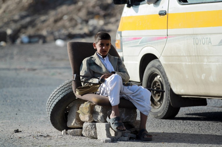 """An armed Yemeni Shiite Huthi rebel child mans a checkpoint erected in the capital Sanaa. Yemeni President Abdrabuh Mansur Hadi vowed to restore state authority and warned of """"civil war"""" in the Sunni-majority country as Shiite rebels were seen in near-total control of the capital. (Mohammed Huwais/Getty Images)"""