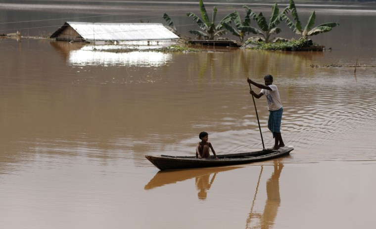 An Indian villager paddles a boat through floodwaters past a partially-submerged house at Balbala village, some 140 kms from Guwahati, the capital of the northeastern state of Assam. At least 55 people have been killed and hundreds of thousands displaced in flash floods and mudslides in India's northeast after days of heavy rain, local authorities said September 24. The chief minister of the northeastern state of Meghalaya, where 35 people have died, said the floods were the worst in recent memory, and bad weather was hampering the rescue effort. (Biju Boro/Getty Images)