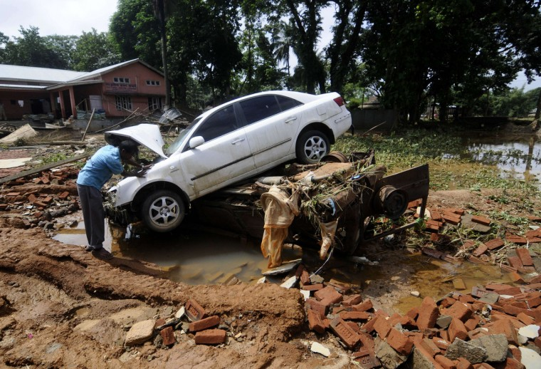 An Indian villager examines a car damaged in flash-floods at Krishnai village, some 125 kms from Guwahati, the capital of the northeastern state of Assam. At least 55 people have been killed and hundreds of thousands displaced in flash floods and mudslides in India's northeast after days of heavy rain, local authorities said September 24. The chief minister of the northeastern state of Meghalaya, where 35 people have died, said the floods were the worst in recent memory, and bad weather was hampering the rescue effort. (Biju Boro/Getty Images)