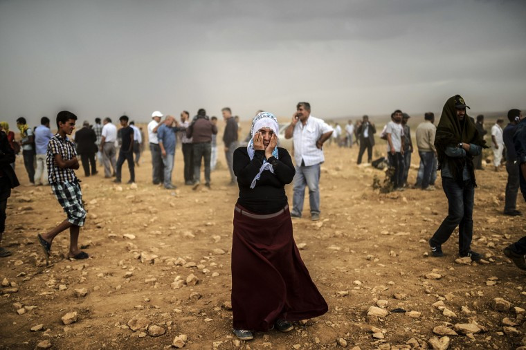 A Syrian Kurdish woman wipes her eyes during a dust storm on a hill where she and others stand watching clashes between jihadists of the Islamic State (IS) and Kurdish fighters, at Swedi village some 10 km west of Suruc in Sanliurfa province,. Tens of thousands of Syrian Kurds flooded into Turkey fleeing an onslaught by the jihadist Islamic State group that prompted an appeal for international intervention. (Bulent Kilic/Getty Images)