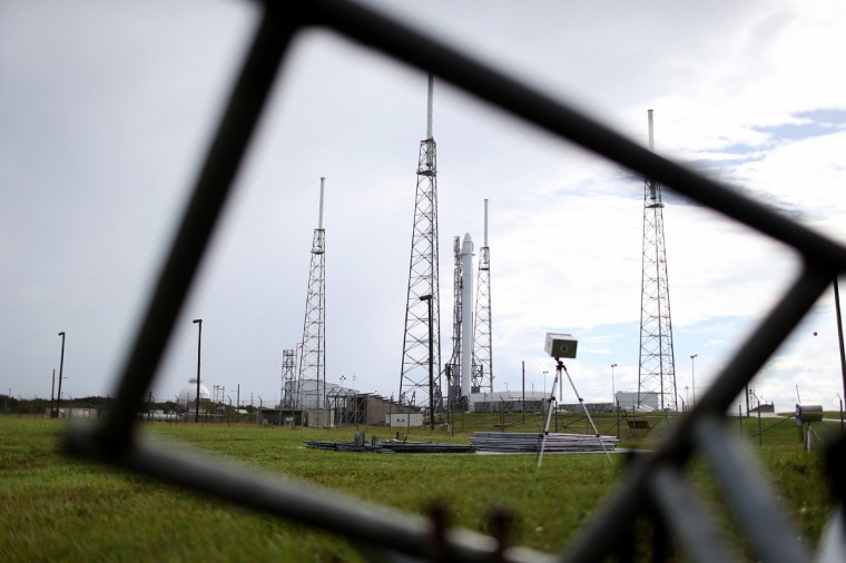 A day after being delayed due to clouds and rain over central Florida the SpaceX Falcon 9 rocket carrying a Dragon supply ship is seen surrounded by lightning protection system towers as it is prepared for the second attempt at launch Sunday at 1:52 am for the resupply trip to the International Space Station September 20, 2014 in Cape Canaveral, Florida. The rocket will bring cargo to the International Space Station. (Photo by Joe Raedle/Getty Images)