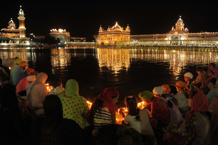 Indian Sikh devotees light candles at the illuminated Sikh shrine, The Golden Temple in Amritsar on September 1, 2014 on the occasion of the 410th anniversary of the installation of the Guru Granth Sahib, the holy book of the Sikh religion. (AFP PHOTO/Getty Images/Narinder Nanu)