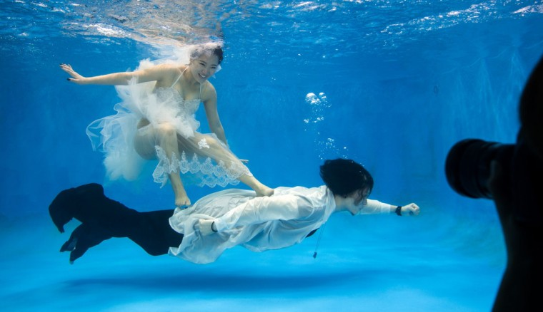 Qin Riyang and Leng Yuting, both 26 years old, posing underwater for their wedding pictures at a photo studio in Shanghai, ahead of their wedding next year. (Johannes Eisele/AFP/Getty Images)