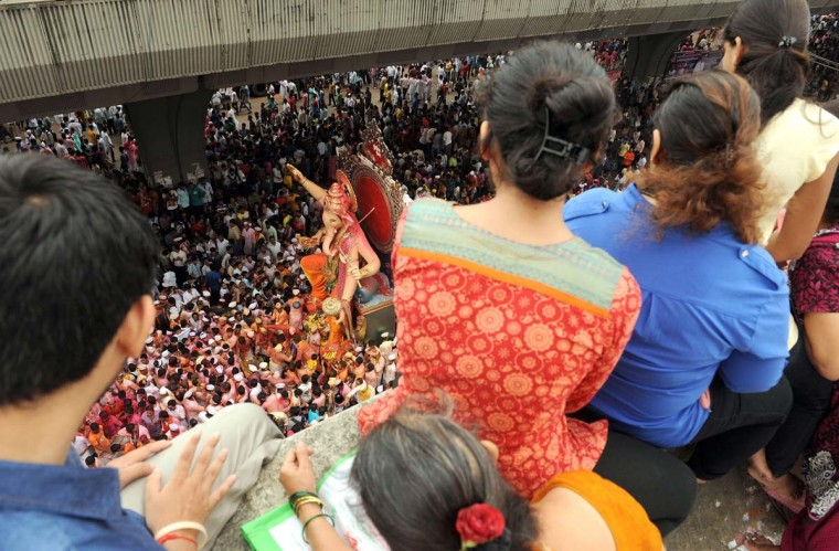 Indians look on from a rooftop as a huge idol of elephant-headed Hindu god Lord Ganesha is brought on procession for an immersion in Mumbai on September 8, 2014. Hindu devotees take idols of the Lord Ganesha - believed to be the harbinger of good health, prosperity and wisdom, at the end of the ten-day long Ganeshotsav festival to be immersed in water bodies. (Indranil Mukherjee/AFP/Getty Images)