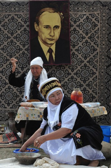 Kyrgyz women cooking in front of the handmade carpet with Russian President Vladimir Putin's portrait during the first World Nomad Games in the Kyrchin (Semenovskoe) gorge, some 300 km from Bishkek. (Vyacheslav Oseledkov/AFP/Getty Images)