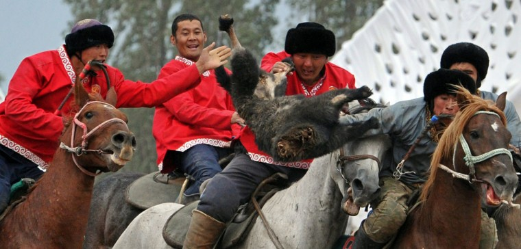 Kyrgyz (red) and Tajik (grey) riders play the traditional Central Asian sport Buzkashi also known as Kok-Boru or Oglak Tartis in the first World Nomad Games in Cholpon-Ata, some 270 km from Bishkek on September 11, 2014 . Mounted players compete for points by throwing a stuffed sheepskin into a well. (Vyacheslav Oseledkov/AFP/Getty Images)