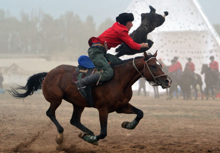 A Kyrgyz rider plays the traditional Central Asian sport Buzkashi also known as Kok-Boru or Oglak Tartis in the first World Nomad Games in Cholpon-Ata, some 270 km from Bishkek on September 11, 2014 . Mounted players compete for points by throwing a stuffed sheepskin into a well. (Vyacheslav Oseledkov/AFP/Getty Images)