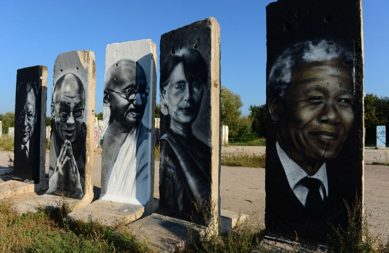 Cement slabs that used to make up the Berlin wall are painted with the portraits of (L to R) German politician Willy Brandt, Tibet's exiled spiritual leader Dalai Lama, leader of Indian independence movement Mahatma Gandhi, Burmese opposition politician Aung San Suu Kyi and South African anti-apartheid revolutionary Nelson Mandela stand in a vacant lot in Teltow outside of Berlin on September 18, 2014. A construction company purchased parts of the wall and offers the possibility to paint them legally after applying for it. (Photos by John MacDougall/AFP/Getty Images)