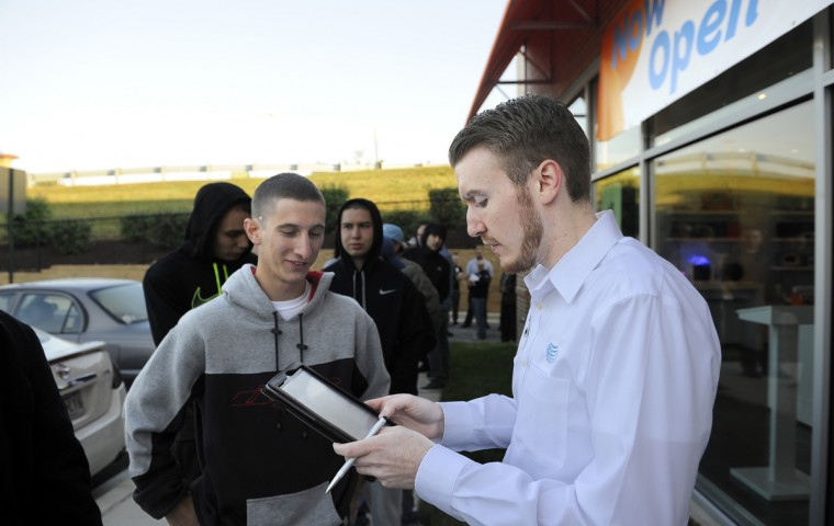 Sam Mullinix of Parkville, left, gives information to Logan Espey, right, assistant store manager of the AT&T store on York road. Dozens of people waited in line to buy the new Apple iphone 6 this morning at the store on York Road. Barbara Haddock Taylor/Baltimore Sun
