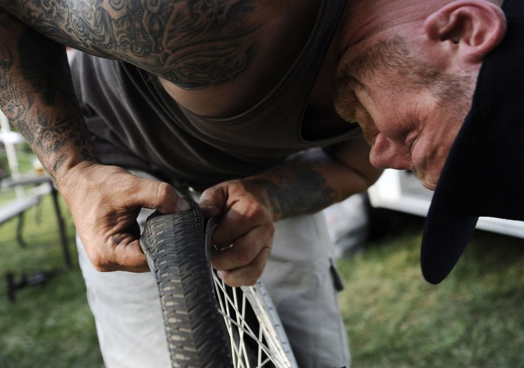 Timm Raum, of Clear Spring, attempts to fix his daughter Ashton Raum's, 19, bike while he passes time at the Quaker State Nationals race weekend in Pottstown, PA. Rachel Woolf/Baltimore Sun