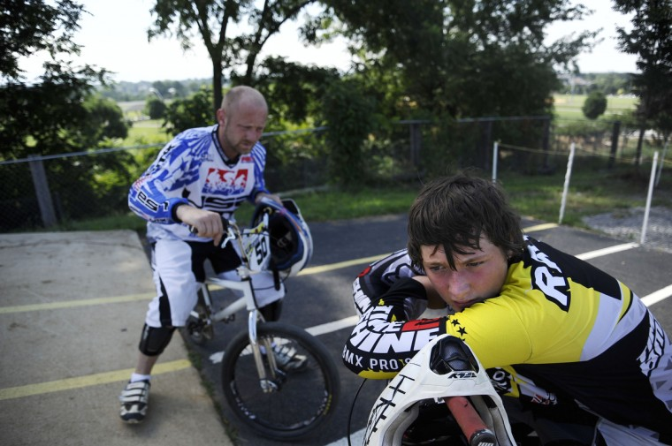 """From left, Timm Raum sits on his bike while his son, Grant Raum, 14, both of Clear Spring, leans on his handlebars during a family practice for a race at the Hagerstown BMX track. Generally, Timm helps coach Grant on how to race. BMX is a type of bicycle racing that means """"bicycle motocross."""" Rachel Woolf/Baltimore Sun"""
