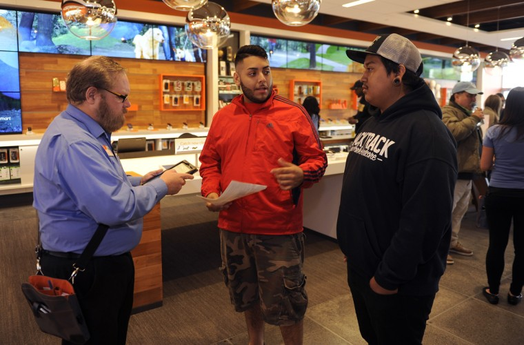 Mark Whiteford, left, a retail sales consultant, works with Juan Martinez, center, and Kevin Cerda, right, both of Baltimore, as they purchase the new Apple iphone 6. Mr. Martinez and Mr. Cerda were the first in line, arriving yesterday evening at 7 to camp outside the store. They joined dozens of others who waited in line to buy the new Apple iphone 6 this morning at the AT&T store on York Road. Barbara Haddock Taylor/Baltimore Sun
