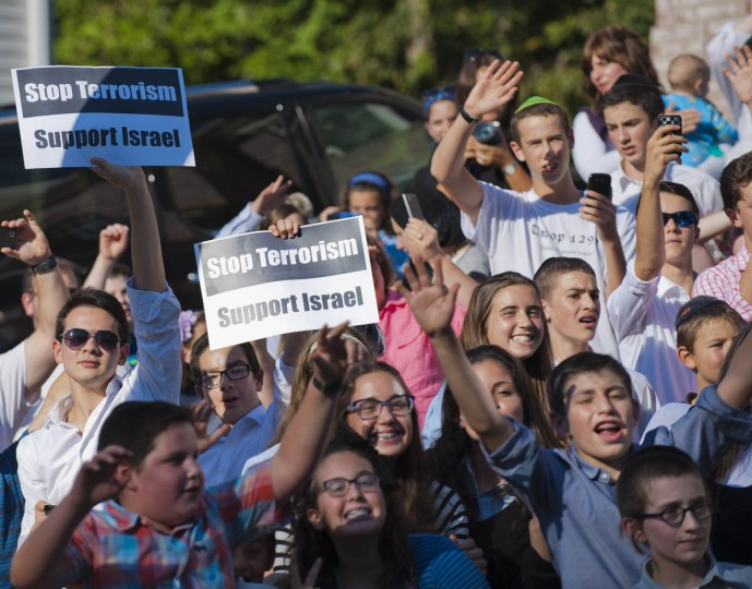 People hold signs as well as wave and smile as the motorcade for President Barack Obama heads for a private residence during a visit of the president to the city and Fort McHenry Friday, Sep 12, 2014. (Karl Merton Ferron / Baltimore Sun)