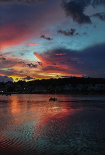 Kayakers row beneath a sunset filled with all hues above Boothbay Harbor. (Karl Merton Ferron/Baltimore Sun)