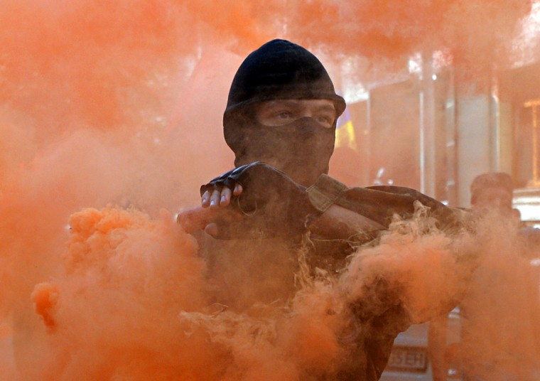 A protestor holds a smoke bomb during a demonstration outside the President Palace in Kiev. Activists from far-right nationalist movements protested against the adoption on September 16, of laws that give extra self-rule powers to some rebel-held territories in the Donetsk and Lugansk regions on eastern Ukraine. (Genya Savilov/Getty Images)