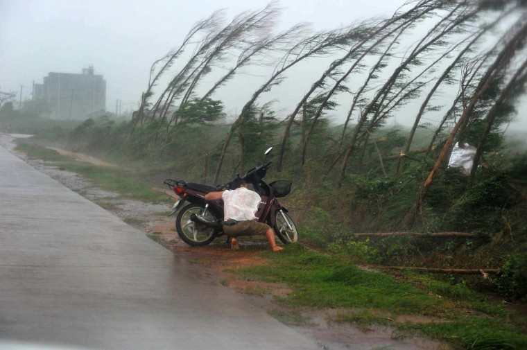 A man takes shelter amid strong rainfall alongside his motorbike in Zhanjiang, south China's Guangdong province. A powerful typhoon slammed into China's Hainan island after sweeping past Hong Kong where it disrupted flights and forced the closure of the stock market and container ports. (Getty Images)