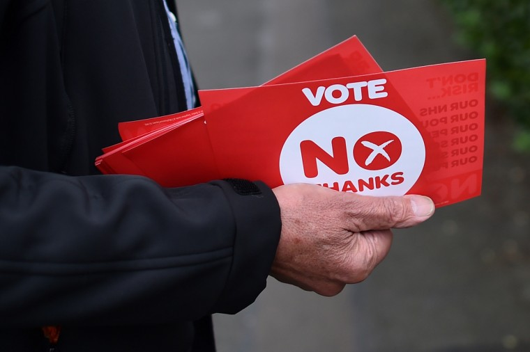 """An anti-independence """"Better Together"""" campaigner carries """"No"""" leaflets in Edinburgh, Scotland on the eve of Scotland's independence referendum. Campaigners for and against Scottish independence scrambled for votes on Wednesday on the eve of a knife-edge referendum that will either see Scotland break away from the United Kingdom or gain sweeping new powers with greater autonomy. (Ben Stansall/Getty Images)"""