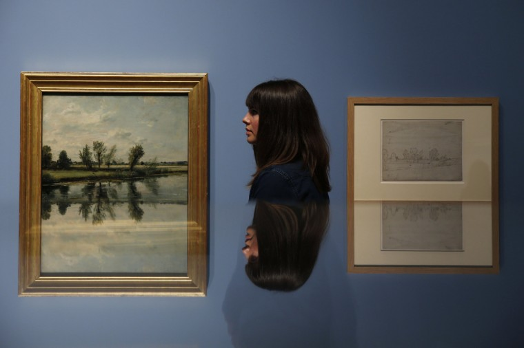 """Museum assistant Emily Williamson poses next to """"Watermeadows at Salisbury"""" (L) by John Constable, during the press view of the """"Constable The Making of a Master"""" exhibition at the V&A museum in London. (Stefan Wermuth/Reuters)"""