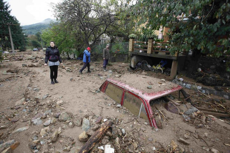 People pass by a vehicle almost completely submerged on a street covered with mud due to heavy floods in Tekija village. One person died in Serbia and authorities scrambled to evacuate hundreds of people from villages threatened by rising rivers, officials said on Tuesday, in scenes recalling the devastating May flooding that killed dozens. (Djordje Kojadinovic/Reuters)