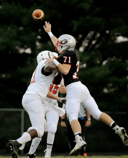 Glenelg's Zach Hahn tries to swat down a pass while Reservoir players try to force him back during a football game at Glenelg High School in Glenelg on Friday, Sept. 19. (Staff photo by Jon Sham, Baltimore Sun Media Group)