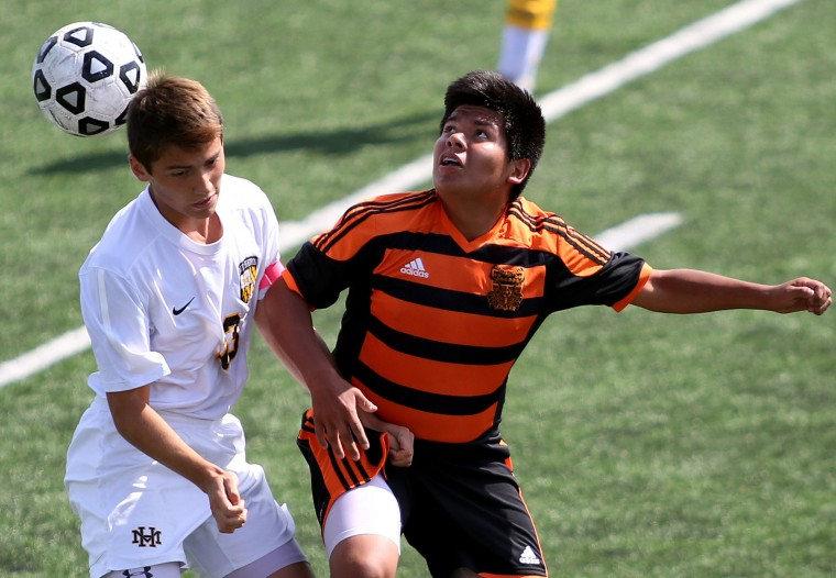 Mt. Hebron senior Brady Burman-Magday, left, fights for possession against Oakland Mills junior Joel Estrada. (Photo by Daniel Kucin Jr., Baltimore Sun Media Group)