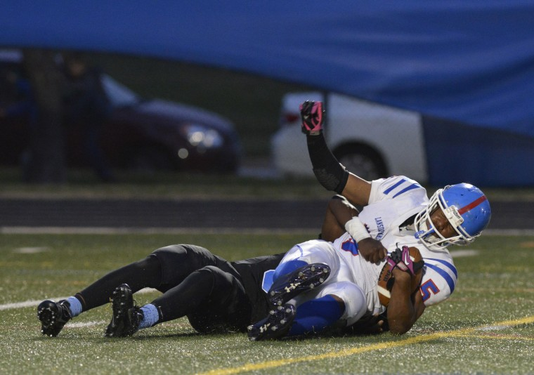Lansdowne's Cornelius Monroe holds onto the ball as he gets tackled in Friday night's game against Western Tech. (Photo by Nicole Munchel, Baltimore Sun Media Group)