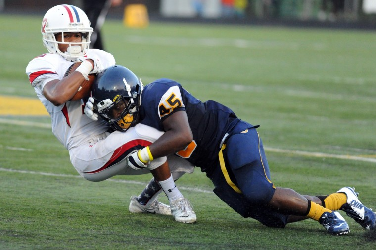 Catonsville's Trey Glover makes a tackle on Thomas Johnson's Adonis Phillips during a football game at Catonsville on Friday, Sept. 5. (Brian Krista/BSMG)