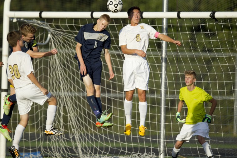 Marriotts Ridge's Brady Trenchard, left, and Hammond's Ben Whong, center, go up for the ball during the boys soccer game at Hammond High School in Columbia on Tuesday, September 23, 2014. (Jen Rynda/BSMG)