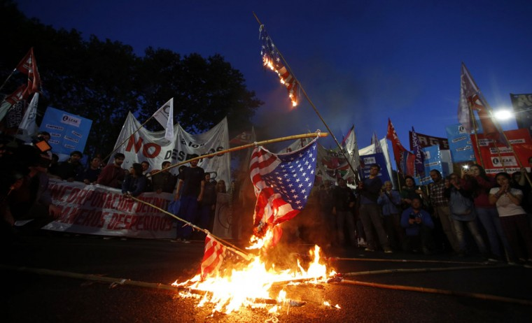 Demonstrators burn U.S. flags during a protest against layoffs at U.S. automotive supplier Lear outside the U.S. Embassy in Buenos Aires, September 24, 2014. (REUTERS/Marcos Brindicci)