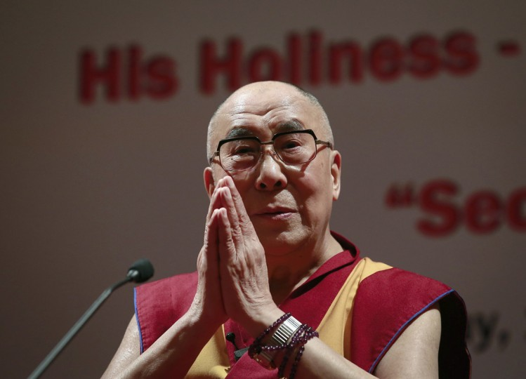 Exiled Tibetan spiritual leader the Dalai Lama gestures during a speech at the 108th anniversary of Indian Merchant Chambers in Mumbai September 18, 2014. Tibet's exiled spiritual leader said on Thursday that an unsettled border with China encompassing large parts of the Tibetan plateau was a problem for India and called for talks to resolve the dispute as Chinese President Xi Jinping toured India. (Danish Siddiqui/Reuters)