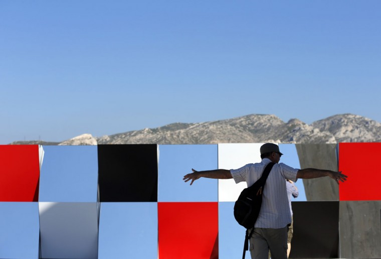 "A visitor gestures as he walks past a creation as part of the exhibition ""Defini Fini Infini, Travaux in situ"" by French artist Daniel Buren at the MaMo art center in Marseille September 12, 2014. (Photos by Jean-Paul Pelissier/Reuters)"