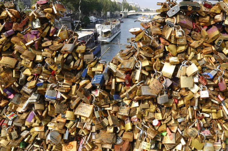 """Padlocks clipped by lovers are seen on the fence of the Pont des Arts over the River Seine in Paris. A city hall campaign to save the bridges of Paris from the weight of hundreds of thousands of brass """"love locks"""" has not checked the ardour of droves of tourists, who continue to view the City of Light as the City of Love. Iron grills lining the bridges have since 2008 been increasingly covered by brass locks purporting to symbolize the unending love of visiting tourists. The city has begun to install thick plastic panels on the Pont des Arts, depriving lovers of the grillwork needed to affix their locks. (Jacky Naegelen/Reuters)"""