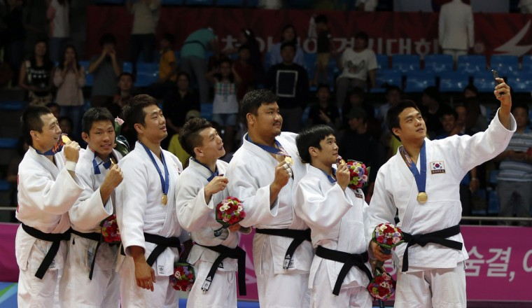 """South Korea's team take a """"selfie"""" with their gold medals after defeating Kazakhstan's team in their men's team gold medal judo contest at Dowon Gymnasium during the 17th Asian Games in Incheon September 23, 2014. (Issei Kato/Reuters)"""
