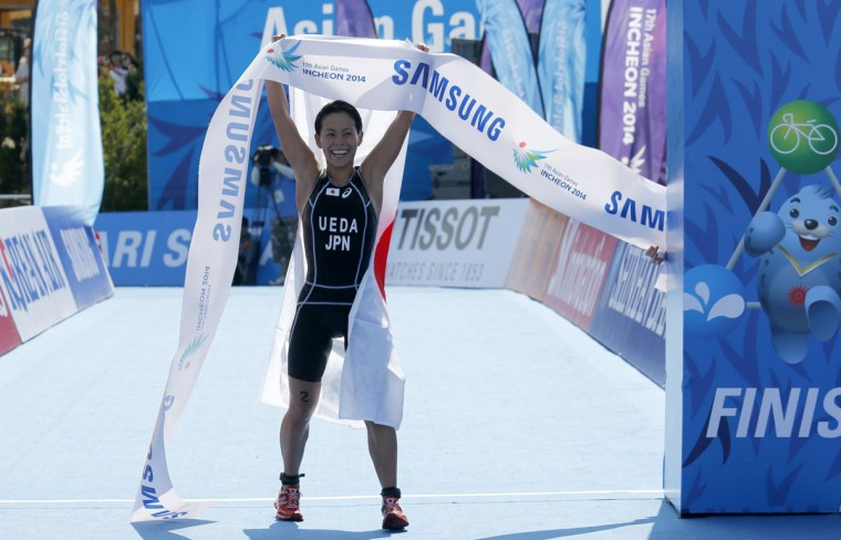 Gold medallist Ai Ueda of Japan holds up the finish line ribbon during the women's triathlon competition at Songdo Central Park at the 17th Asian Games in Incheon September 25, 2014. (REUTERS/Kim Kyung-Hoon)