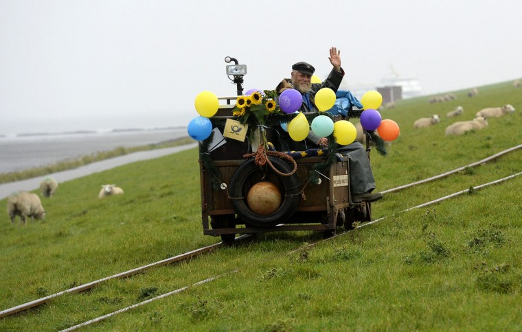 Postman Fiete Nissen, 64, waves as he drives his trolley along the track on his way from the coast of Dagebuell, some 180 kilometers north of Hamburg, to the tiny North Sea islands of Oland and Langeness on his last working-day, September 30, 2014. Nissen was the official postman for the islands' 139 residents for more than 37 years. (REUTERS/Fabian Bimmer)