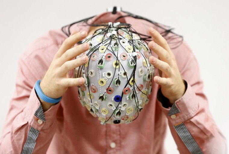 Test person Niklas Thiel poses with an electroencephalography (EEG) cap which measures brain activity, at the Technische Universitaet Muenchen (TUM) in Garching near Munich September 9, 2014. The researchers from TUM and the Technische Universitaet Berlin (team Phypa) try to find ways to control an airplane with computer translated brain impulses without the pilot touching the plane's controls. The solution, if achieved, would contribute to greater flight safety and reduce pilots' workload. Picture taken September 9, 2014. REUTERS/Michaela Rehle