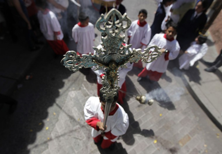 A choir boy holds a cross while another swings an incense censer during a procession in celebration of the 436th anniversary of the founding of Tegucigalpa September 29, 2014. (REUTERS/Jorge Cabrera)