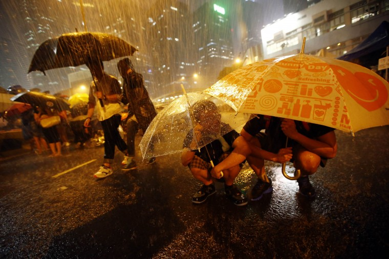 Protesters take shelter from the rain under umbrellas as they block the main street to the financial Central district outside of the government headquarters in Hong Kong, September 30, 2014. Tens of thousands of pro-democracy protesters extended a blockade of Hong Kong streets on Tuesday, stockpiling supplies and erecting makeshift barricades ahead of what some fear may be a push by police to clear the roads before Chinese National Day. (Carlos Barria/Reuters)