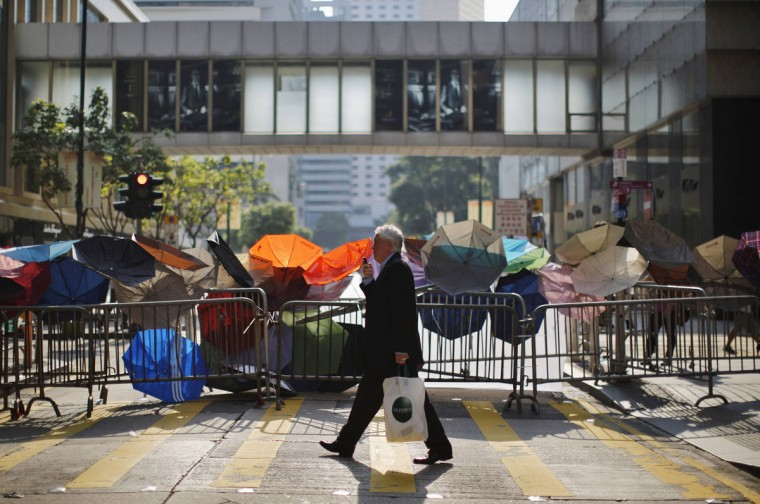 A man walks by a barricade of metal fence and umbrellas on a street at the central financial district, near the government headquarters in Hong Kong September 30, 2014. Tens of thousands of pro-democracy protesters extended a blockade of Hong Kong streets on Tuesday, stockpiling supplies and erecting makeshift barricades ahead of what some fear may be a push by police to clear the roads before Chinese National Day. (REUTERS/Carlos Barria)