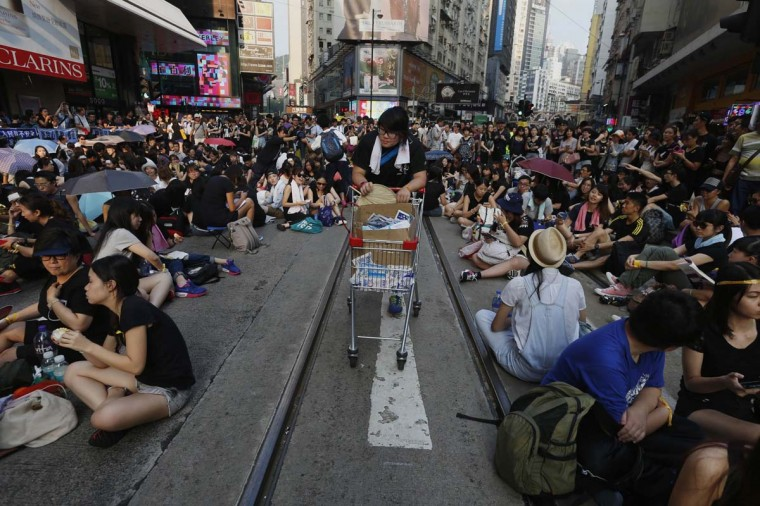 A student provides supplies on a tram track as thousands of students occupy a main street at Causeway Bay shopping district in Hong Kong September 29, 2014. Increasing civil unrest in Hong Kong is scaring off Chinese tourists, heaping further pressure on retailers which are already grappling with a protracted slowdown in sales. (Bobby Yip/Reuters)