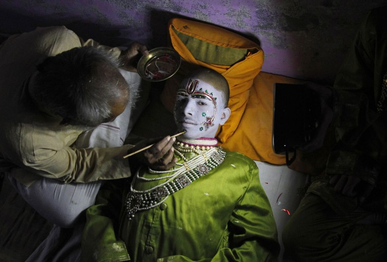"""Amit Kumar, 14, a performer, gets makeup applied before performing the role of the Hindu lord Rama in a religious play ahead of Dussehra in the northern Indian city of Allahabad September 30, 2014. Effigies of the 10-headed demon king """"Ravana"""" are burnt on Dussehra, the Hindu festival that commemorates the triumph of Lord Rama over the Ravana, marking the victory of good over evil. (REUTERS/Jitendra Prakash)"""