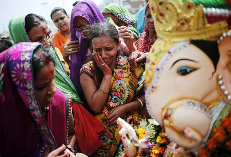 A devotee (C) cries as others prepare to immerse an idol of Hindu god Ganesh, the deity of prosperity, on the banks of the river Yamuna in New Delhi September 8, 2014. Ganesh idols are taken through the streets in a procession accompanied by dancing and singing, and later immersed in a river or the sea symbolising a ritual seeing-off of his journey towards his abode, taking away with him the misfortunes of all mankind. (Anindito Mukherjee/AFP/Getty Images)