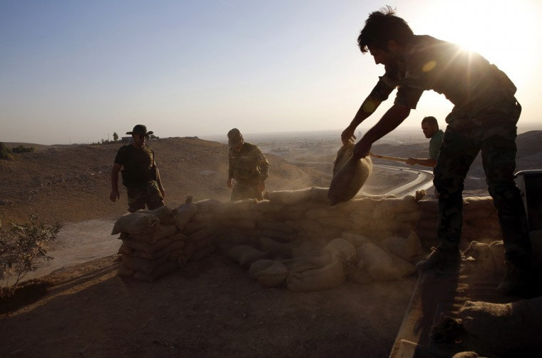 A Kurdish Peshmerga fighter uses sandbags to make a gun placement over-looking the road to Makhmur that was retaken from the Islamic Sate, south of Erbil September 10, 2014. (Ahmed Jadallah/Reuters)